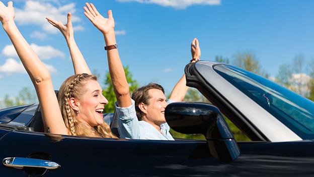 Ein junges Paar sitzt vergnügt in einem blauen Cabriolet.