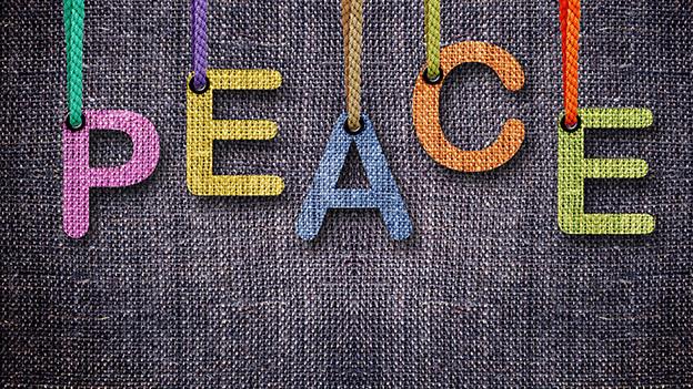 Farbige Buchstaben aus Holz, die das Wort Peace ergeben.