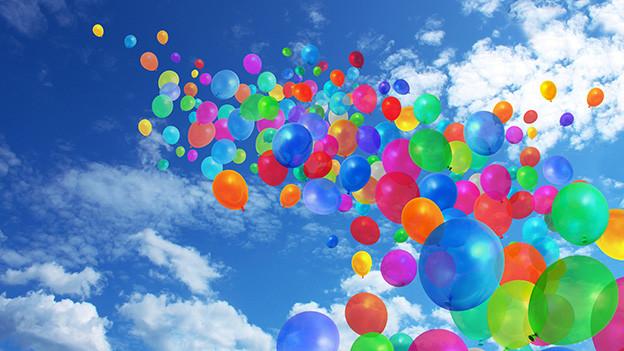 Viele bunte Luftballons am blauen Himmel.