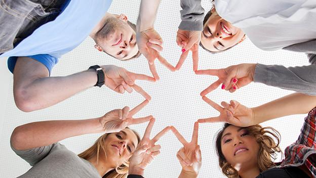 Vier junge Menschen, die mit ihren Fingern gemeinsam ein Symbol der Einigkeit bilden.