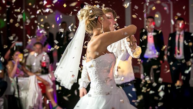 Ein Hochzeitspaar tanzt unter Konfettiregen.