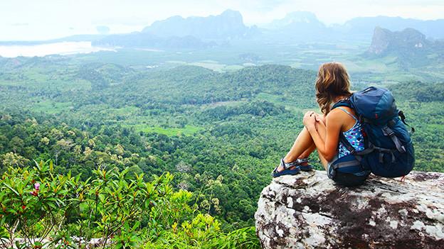 Eine junge Frau mit Rucksack sitzt auf einem Felsen und blickt in die Ferne.