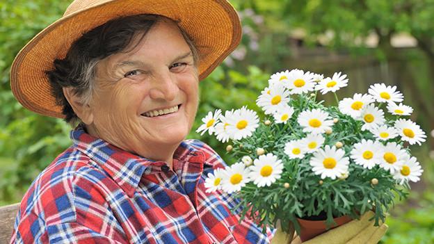 Eine Frau mit Sonnenhut und kariertem Hemd hält einen Topf mit Margriten in den Händen.