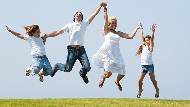 Ein Mann, eine Frau und zwei Kinder springen Hände haltend fröhlich in die Luft.