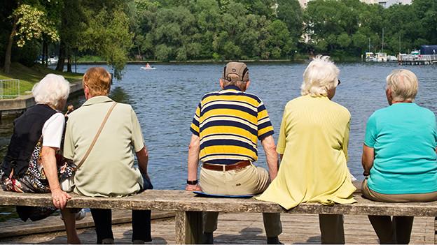 Eine Gruppe älterer Menschen sitzt auf einem Steg am Seeufer.