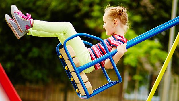 Ein kleines Mädchen auf einer Schaukel.