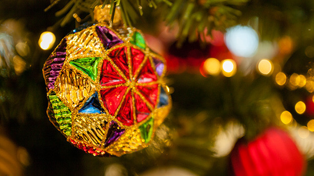 Eine Weihnachtskugel in verschiedenen Farben an einem Tannenbaum.