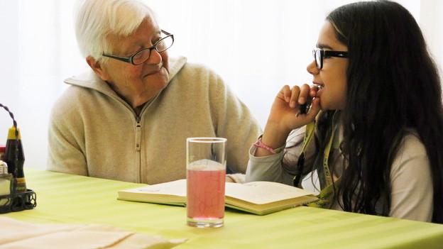 Seniorin liest mit Mädchen ein Buch an einem Holztisch.