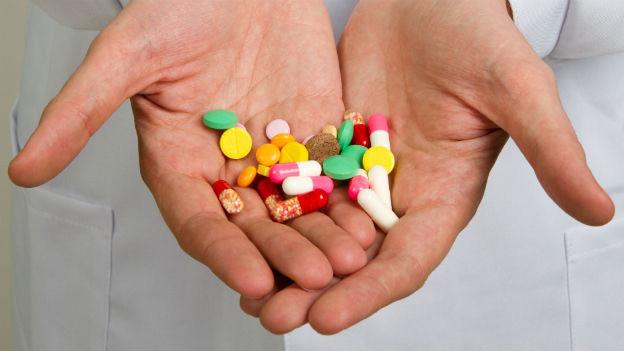 Eine Hand, in der Pillen in verschiedenen Farben liegen.