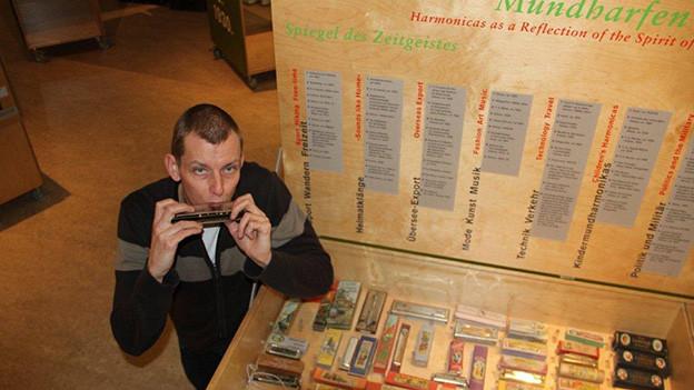 Ein Mann steht neben einer Vitrine, in der viele verschiedene Mundharmonikas liegen.
