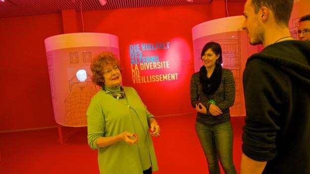 Seniorin im Museum mit Besuchergruppe.