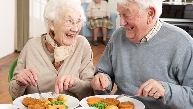 Eine ältere Frau und ein älterer Mann sitzen fröhlich und zufrieden vor ihren Tellern mit Schnitzel, Kartoffeln und Gemüse.