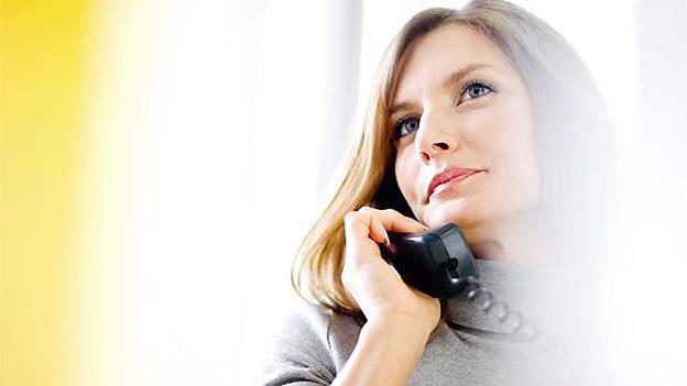 Eine blondhaarige Frau hält einen dunklen Telefonhörer ans Ohr.