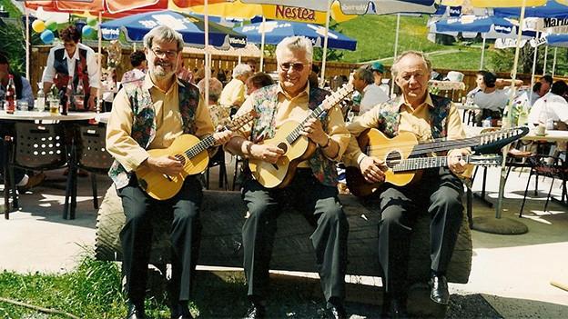 Drei Musiker in gelben Hemden und bunten Gilets sitzen mit ihren Instrumenten auf einem Baumstamm.