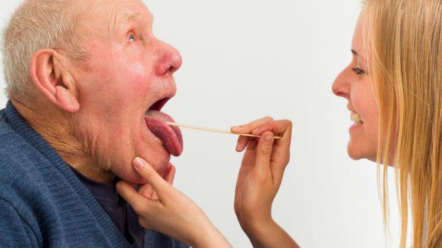 Ärztin schaut Senior in den Mund.