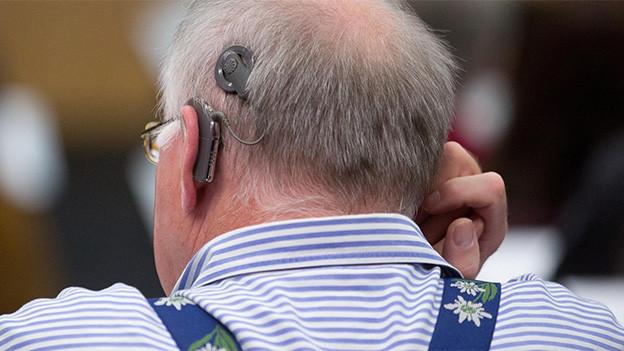 Hinterkopf eines Mannes, der ein Hörgerät trägt.
