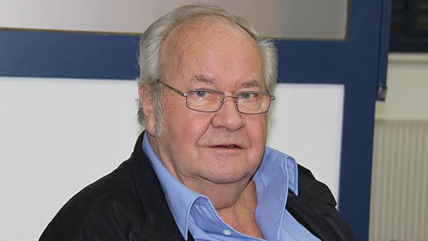 Ein Mann mit grauen Haaren und Brille, der ein hellblaues Hemd und eine dunkle Jacke trägt.