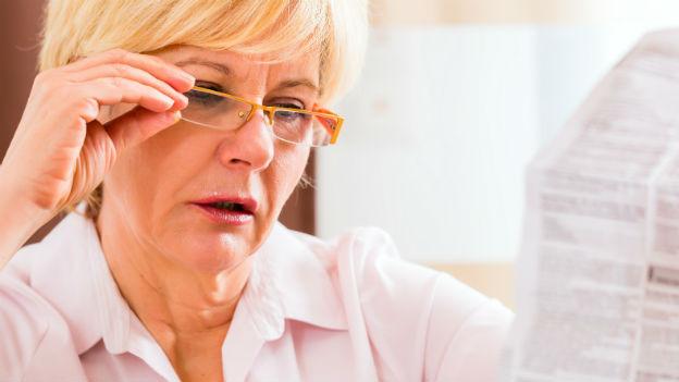Frau liest Packungsbeilage von Medikament.