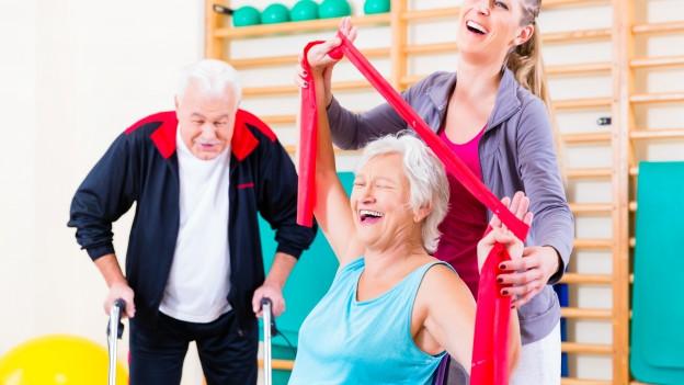 Zwei Senioren turnen mit Stretchbändern.