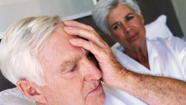 Senior hält sich unter Schmerzen Hand an Kopf