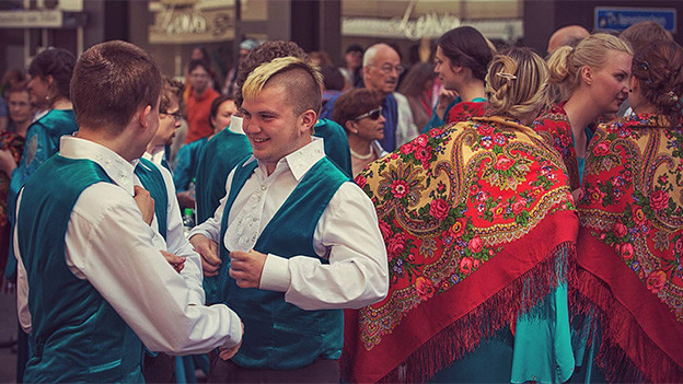 Junge Sängerinnen und Sänger in farbiger Kleidung im angeregten Gespräch nach einem Konzert.