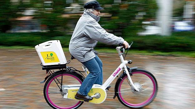 Eine ältere Frau fahrend auf einem E-Bike.