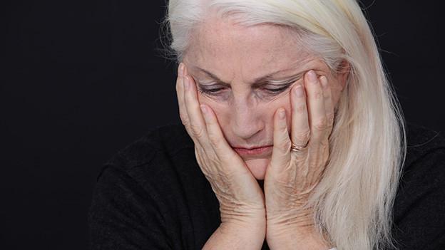 Eine ältere Frau hält sich betroffen die Hände ans Gesicht.