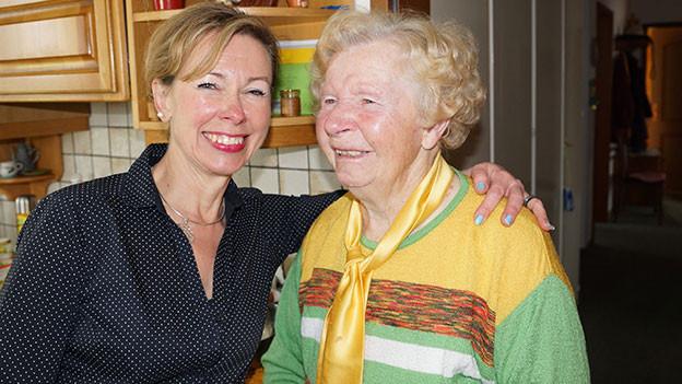 Eine jüngere und eine ältere Frau stehen nebeneinander in einer Küche.