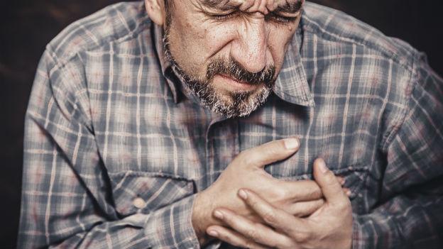 Mann hält seine Brust.