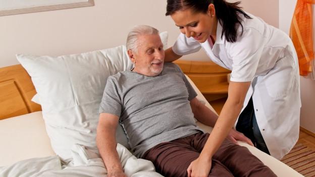 Frau pflegt älteren Mann.