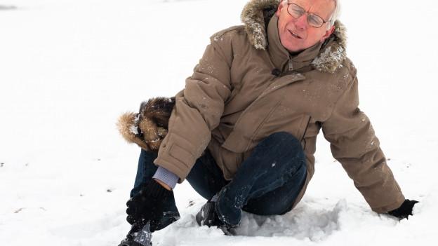 Älterer Mann stürzt auf Schnee.