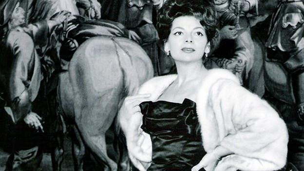 Lys Assia ganz edel mit Pelz udn Samtkleid vor Gemälde mit Pferden.