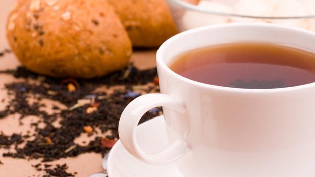 Tasse Tee un d daneben ein Brötchen.