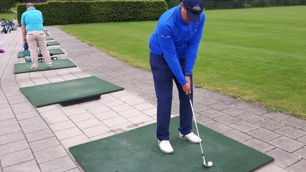 Golfer übt Abschlag auf Driving Range.