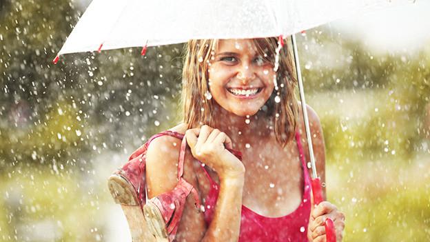 Eine junge sommerlich gekleidete Frau unter einem Regenschirm.