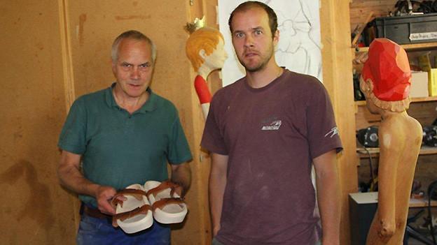 Ein älterer und ein jüngerer Mann stehen in einer Holzwerkstatt.