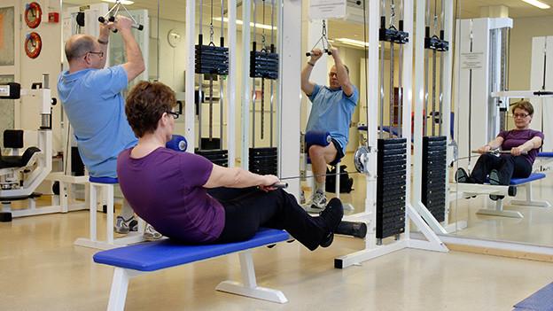 Ein älteres Ehepaar trainiert in einem Fitness-Club.