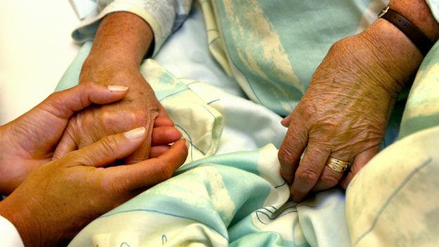 Junge Hände halten alte Hände.