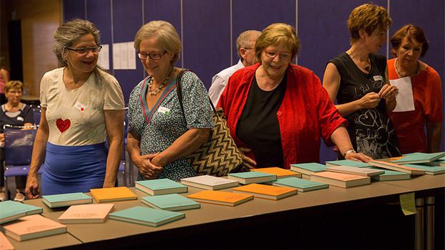 Eine Gruppe von Frauen steht vor einem langen Tisch, auf dem viele Bücher liegen.
