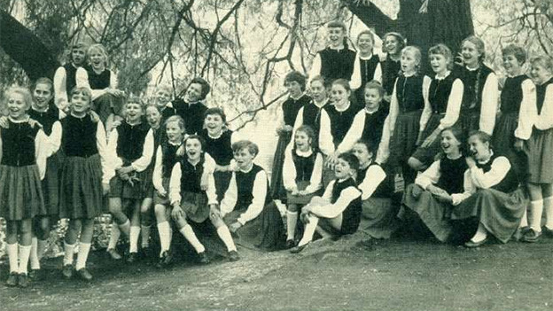 Schwarz-Weiss-Fotografie mit einem Kinderchor, der auf einer Treppe steht.