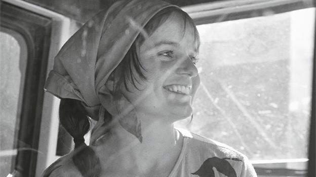 Die Schwarz-Weiss-Fotografie zeigt eine junge lachende Frau mit Kopftuch.