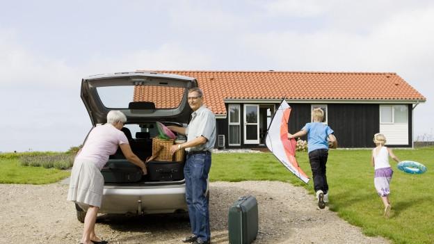 Grosseltern laden Koffern aus dem Auto während die Enkel spielen.