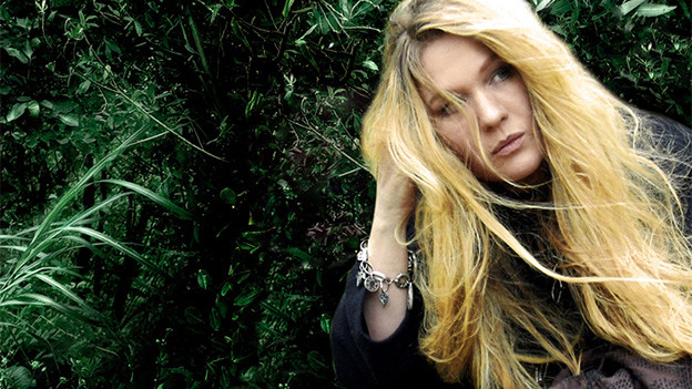 Die Sängerin mit langen blonden Haaren für einem grossen grünen Busch.
