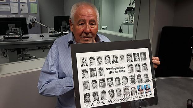 Ein ältere Mann zeigt ein Bild mit Porträts von Schwingerkönigen.