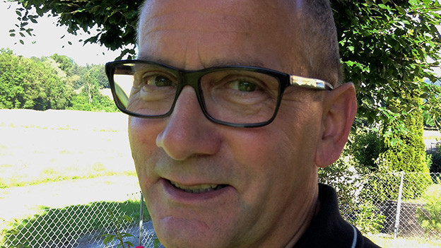Ein Mann mit Brille und schwarzem Polo-Shirt.