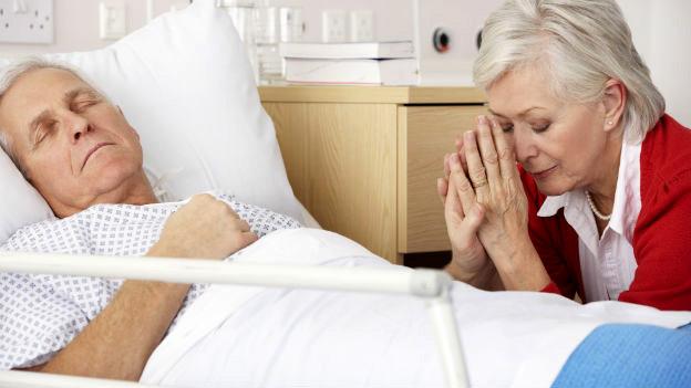Eine Frau sitzt am Bett eines schlafenden Patienten.