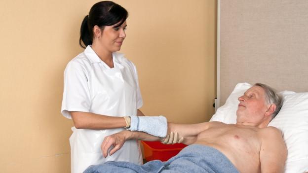 Eine Pflegende hilft einem Patienten bei der Körperpflege