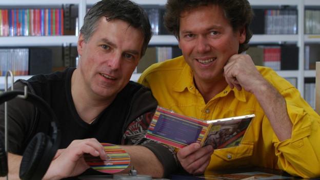 Zwei Musikredaktoren mit CDs.