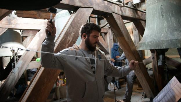 Mann verbindet Glockenschwengel mit Drahtseil.