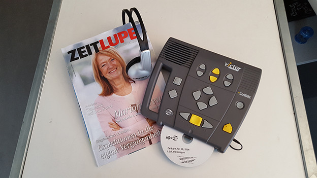 Eine Zeitschrift auf einem Tisch neben einem Abspielgerät.